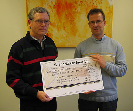 Photo: Dr. Lossau and Dr. Höppner presenting a cheque for Bielefeld Public Library